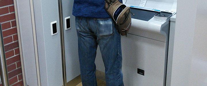 ATMを使用する男性